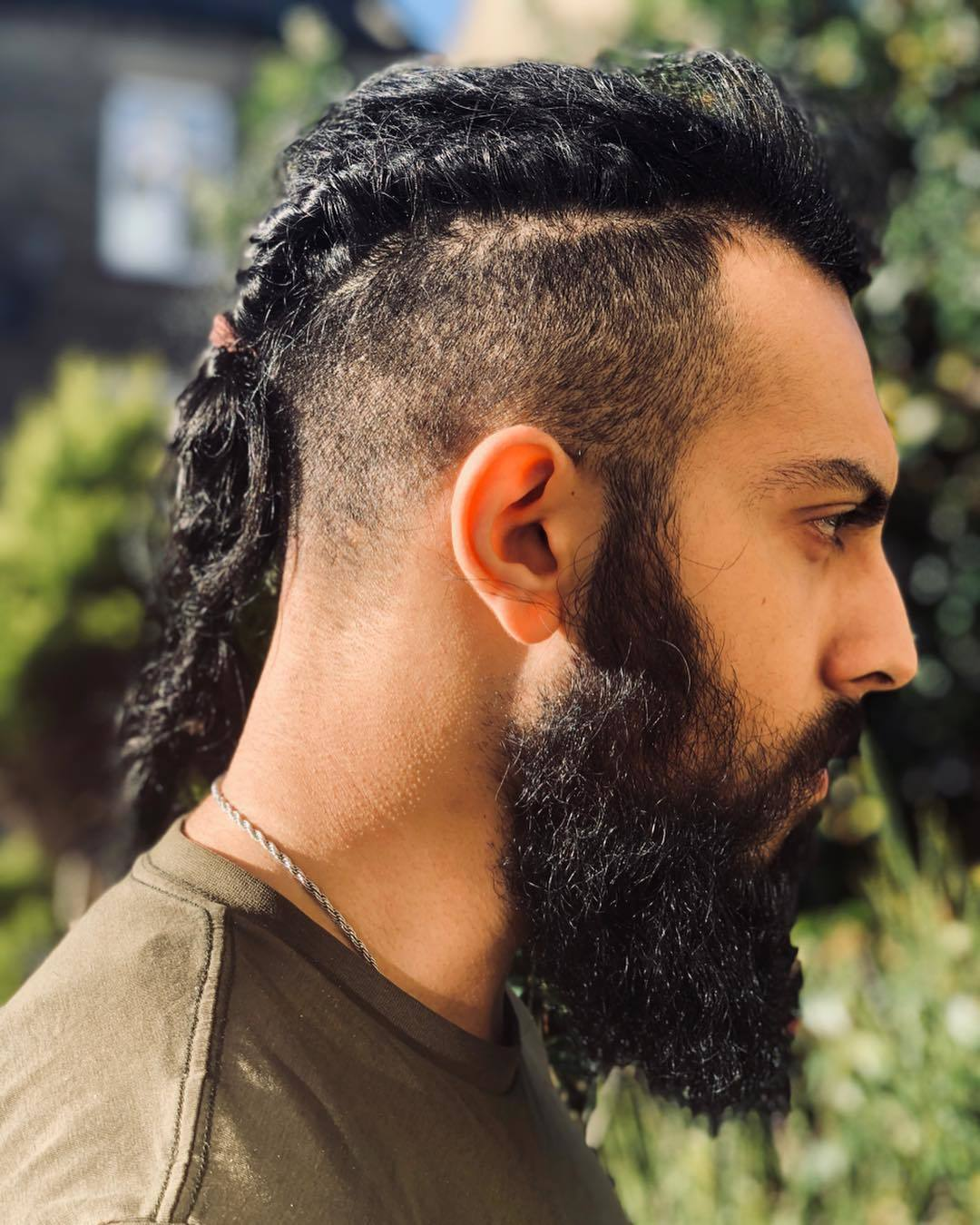 Viking Hairstyles: Man with dark brown thick hair with twisted braid and undercut with thick rugged beard