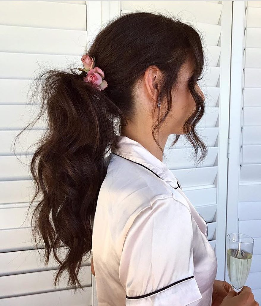 Wavy hair tips brunette girl with wavy ponytail standing to the side