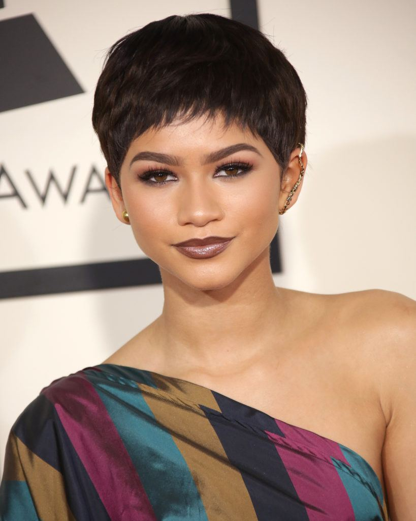 pixie cut black hair: close up shot of zendaya with black hair pixie cut on the grammy award red carpet, wearing nude makeup and colourful dress