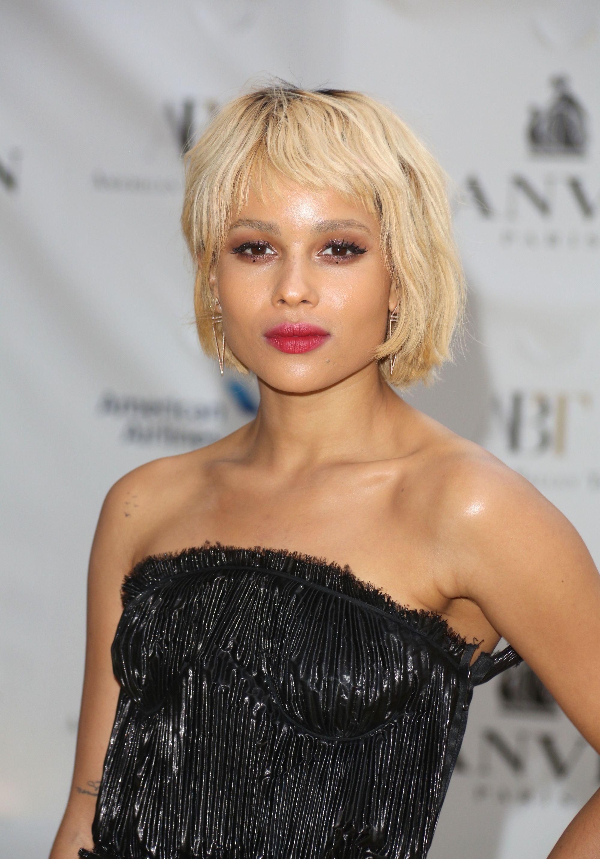 Zoë Kravitz with golden blonde short hair with a wispy micro fringe, wearing all black and posing on the red carpet