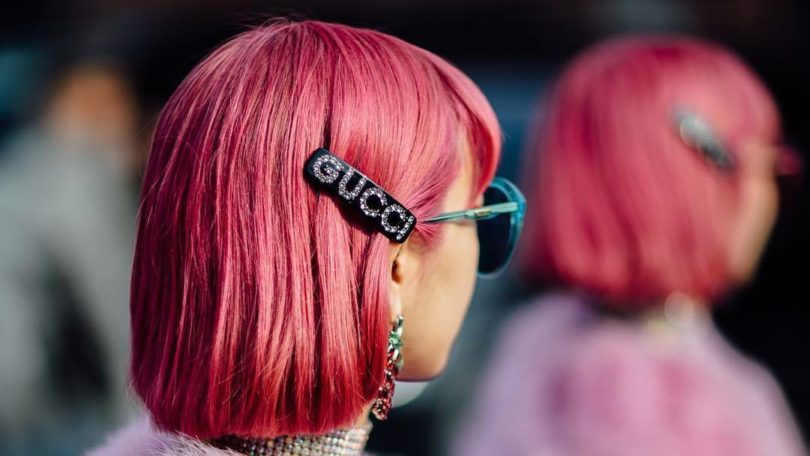 street style model wearing a pink fluffy fur coat and sunglasses with a Gucci hair slide in her short pink bob hairstyle