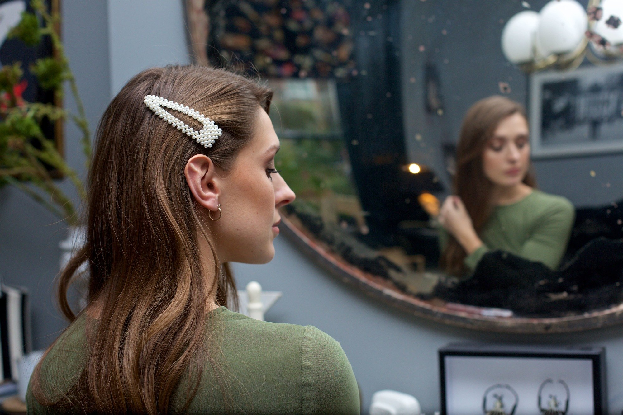 Spring haircuts: Woman with long wavy brunette highlighted hair with an oversized pearl hair clip, doing her hair in the mirror