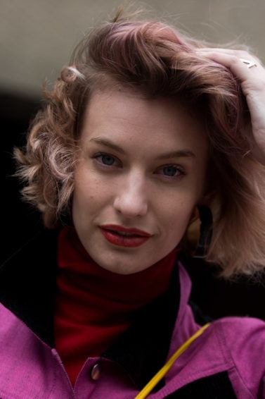 best hair mousse guide: close up street style shot of woman with pastel pink wavy bob, wearing pink jacket and red scarf