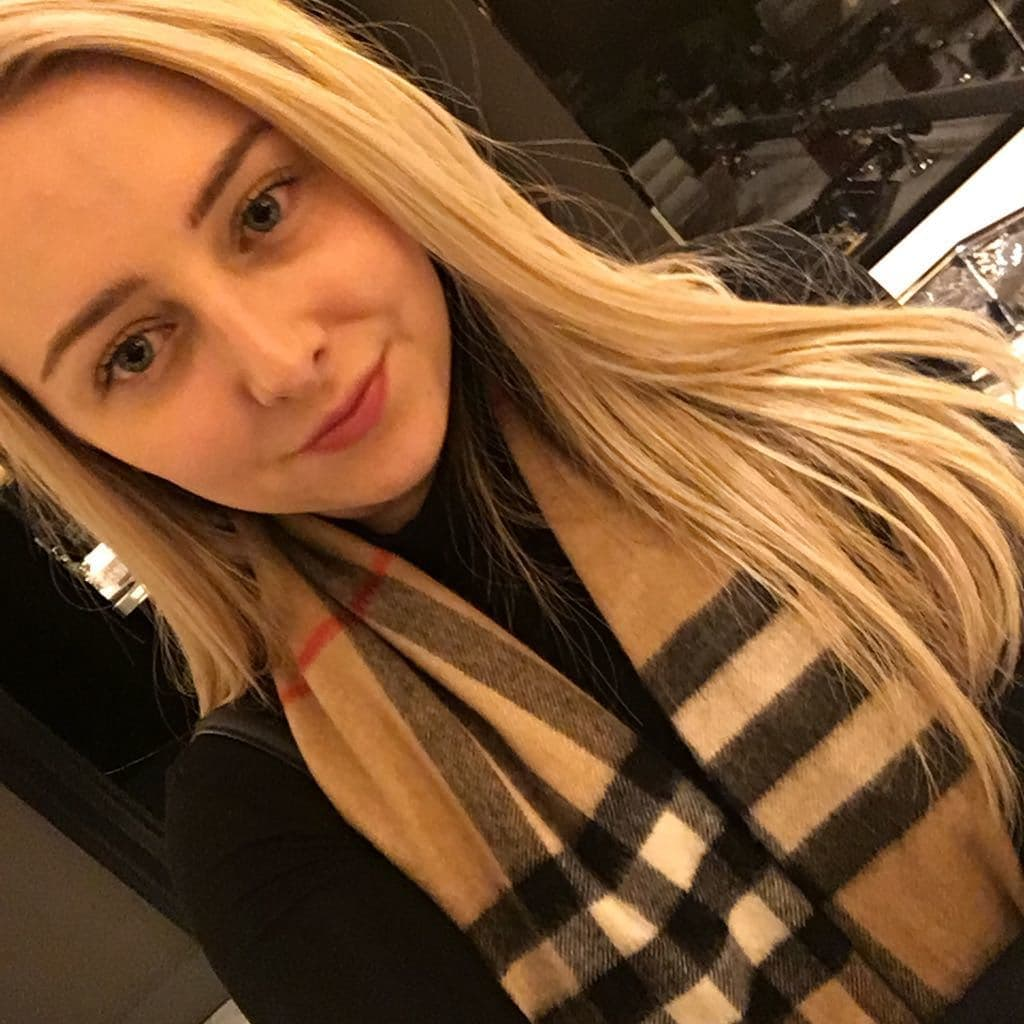 close up shot of woman with sleek blonde hair, wearing scarf and black top