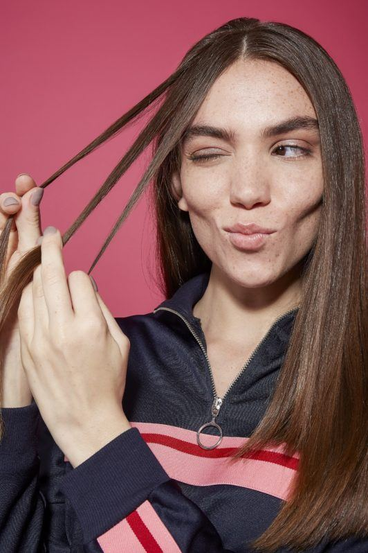 Brunette girl holding three strands of hair to create a boxer braid
