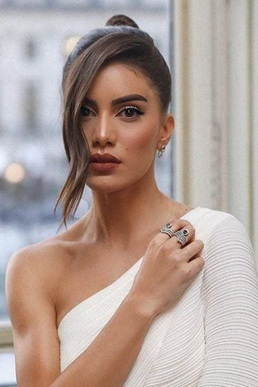 Night out hairstyles: Woman with chestnut brown hair styled into a high sleek bun, with face-framing tendril, wearing white party dress, posing in a hotel