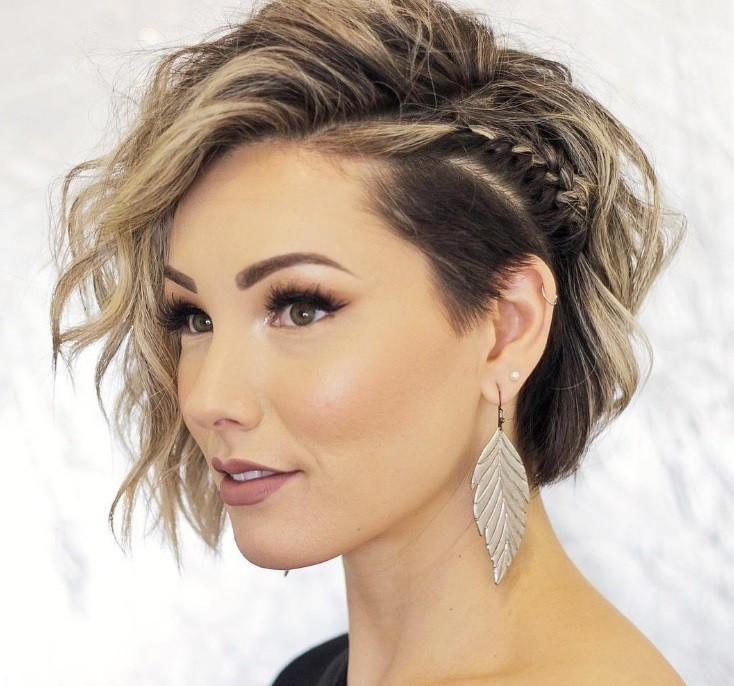 Short night out hairstyles: Woman with short hair with undercut styled into beachy waves, with a side braid in it, posing in a studio setting