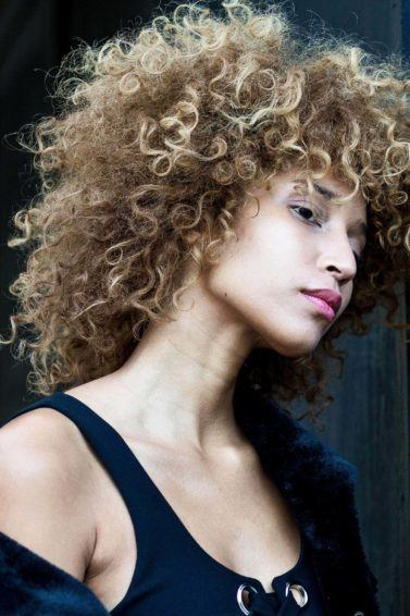 best conditioner for dry hair: close up shot of model with curly hair, touching her hair and wearing blue denim shirt