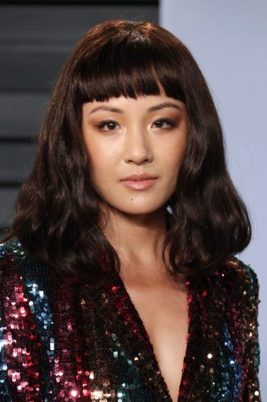 close up shot of constance wu on the red carpet with blunt cut bangs, wearing glittery dress on the oscars red carpet