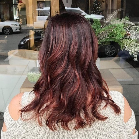 woman with shoulder length curled dark brown and red hair