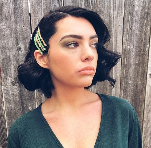 Short night out hairstyles: Woman with short dark brown hair styled into vintage curls, wearing colourful bobby pins in her hair with a green wrap dress, posing outside