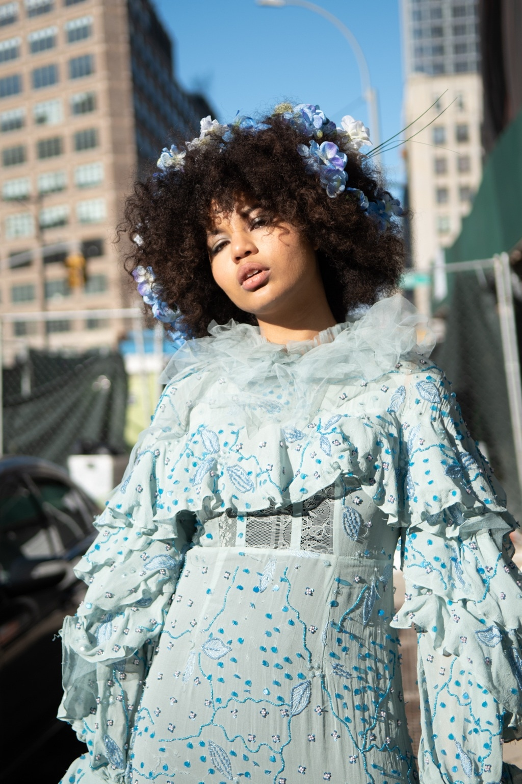Spring haircuts: NYFW street style shot of a woman with afro hair with blue flowers in wearing a matching frilly blue floral dress