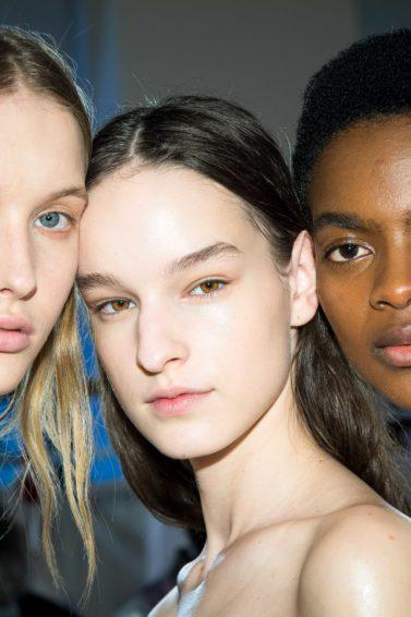Brittle hair: Three models backstage at Giambattista Valli show with different hair types, wavy, straight and short afro.