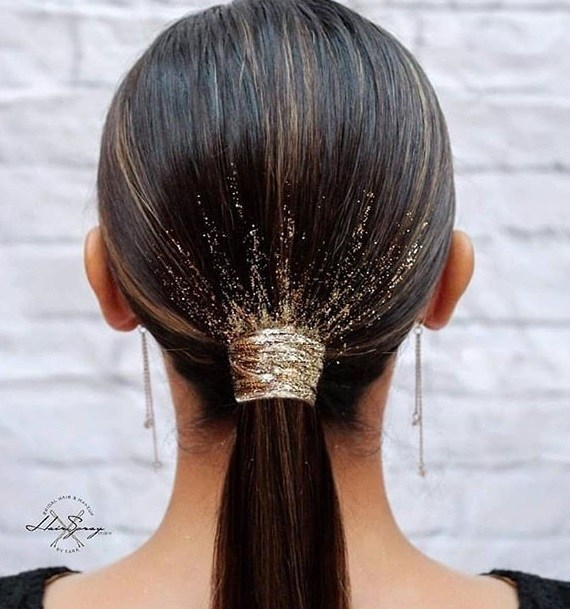 Woman with low, dark brown sleek ponytail with golden glitter around the base, wearing drop earrings and posing against a white wall