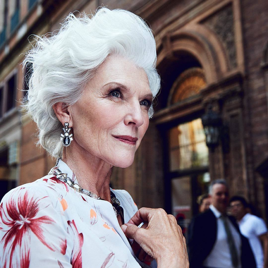 What causes grey hair Maye Musk standing outside in the street