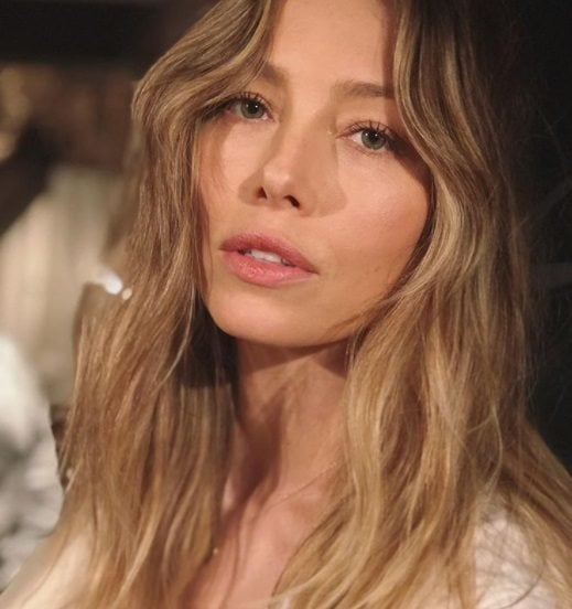 close up shot of jessica biel with wavy bronde hair, wearing white shirt and posing