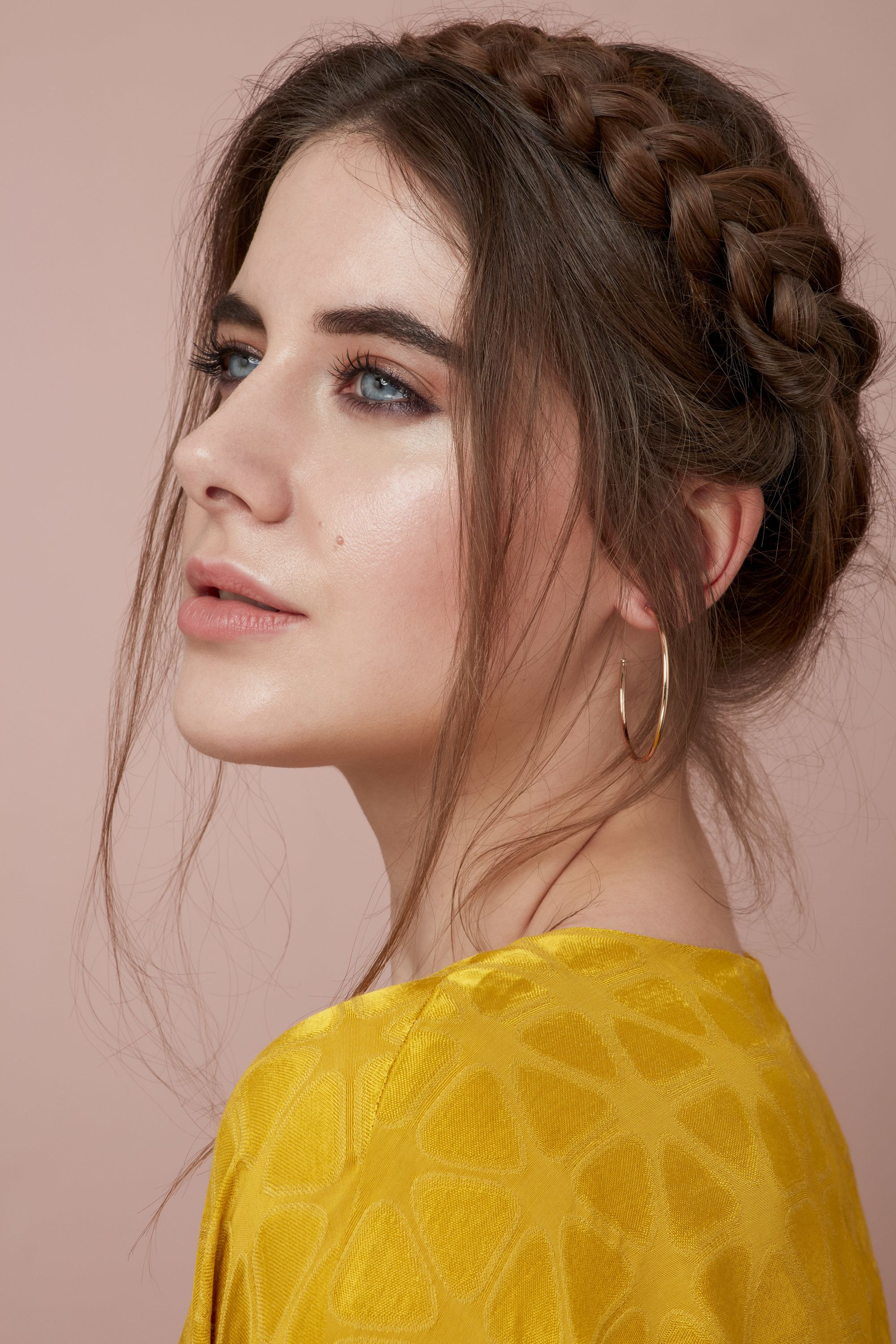 Valentines hair: Close-up of a brunette woman with her hair in a milkmaid braid with loose undone strands, wearing a yellow top