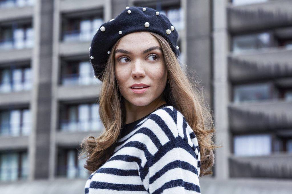 Brunette girl wearing beret standing outside with headband curls