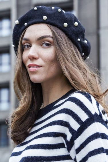 cute long hairstyles: close up shot of model with long wavy hair, wearing stripped top and posing outside with a pearl beret