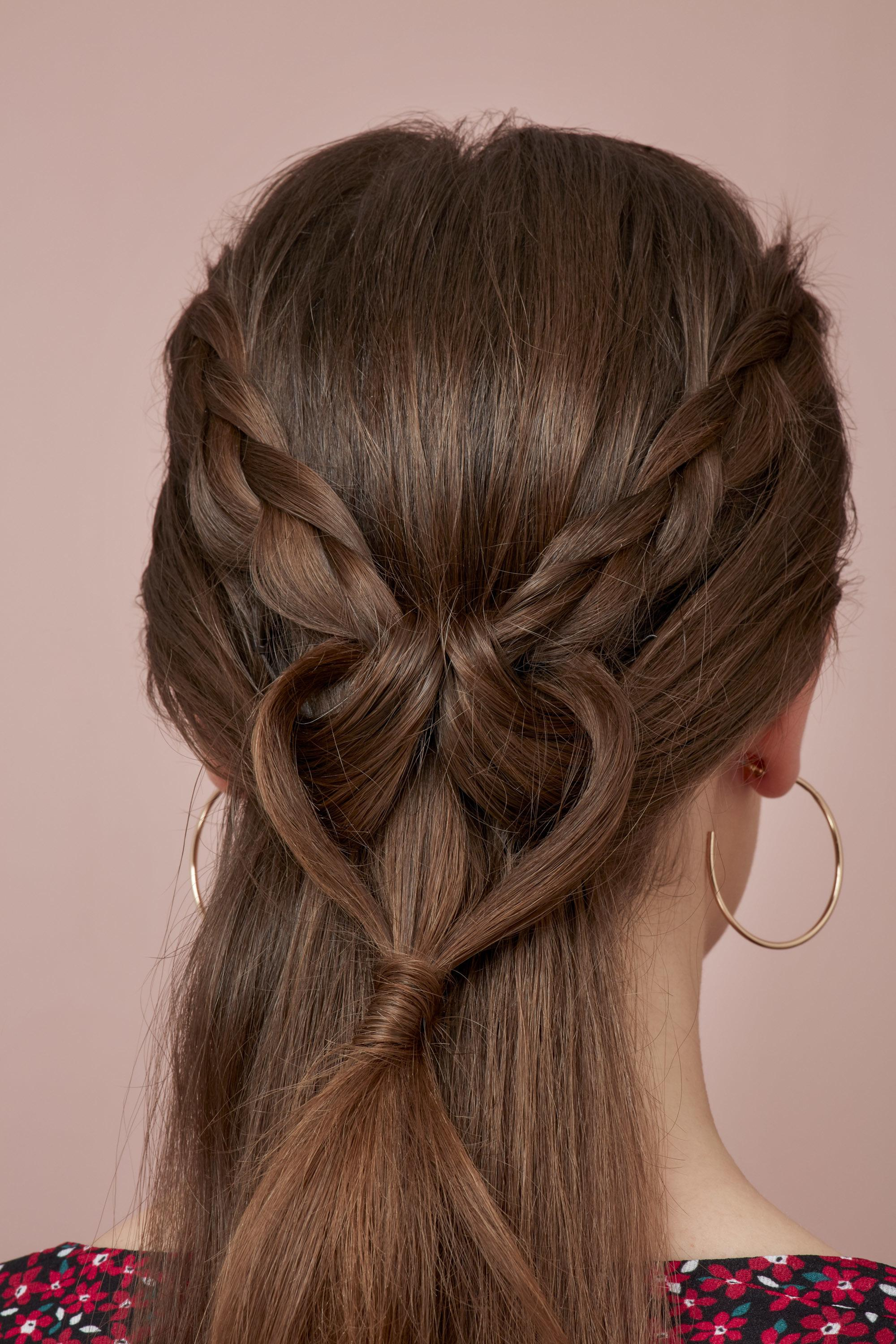 Valentines hair: Close-up back view of a brunette with a half-up braided hairstyle in the shape of a love heart