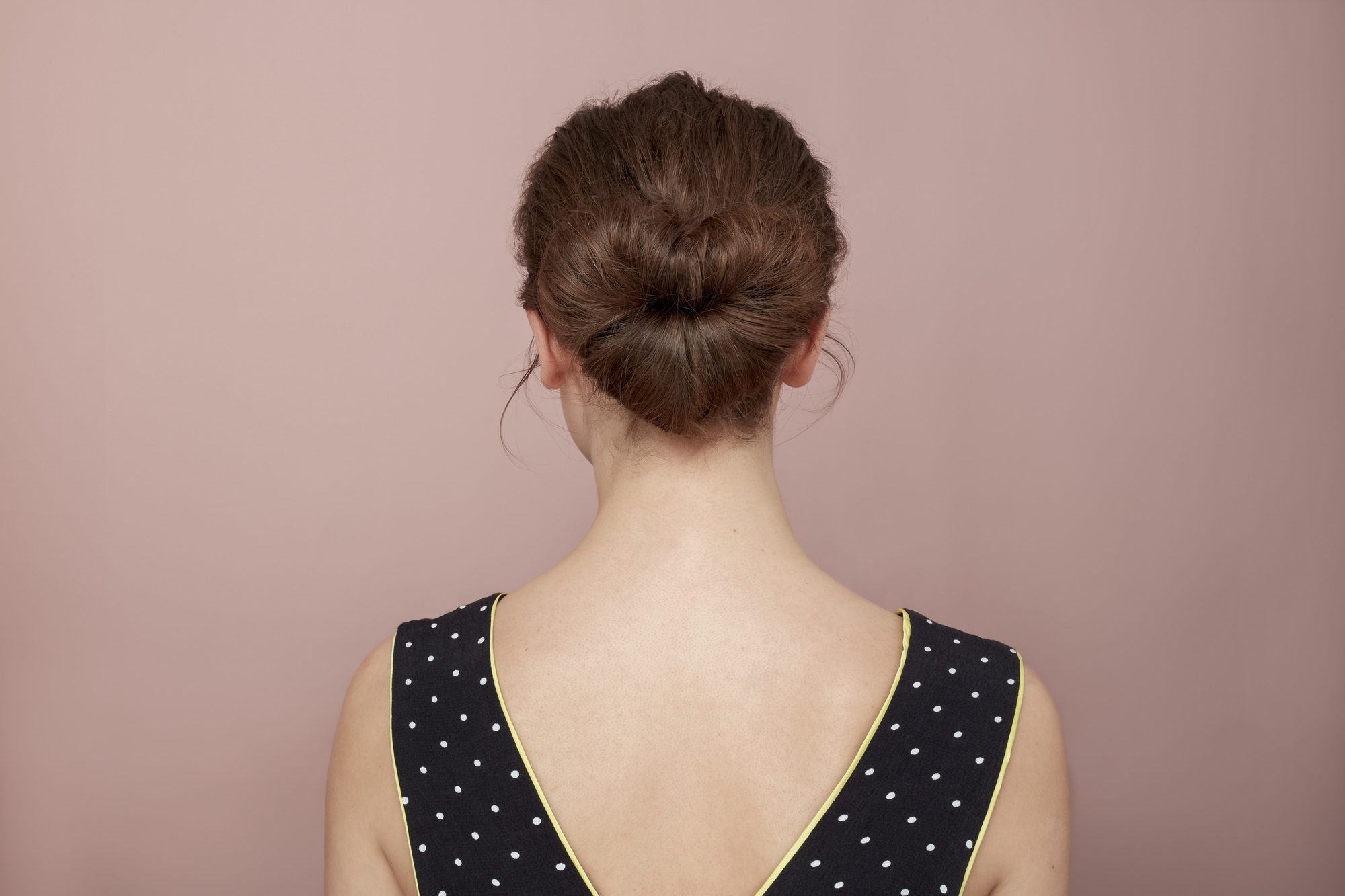 Valentines hair: Back view of a brunette model with her hair in a heart shaped bun, wearing a v-back spotty polka dot black and white dresa