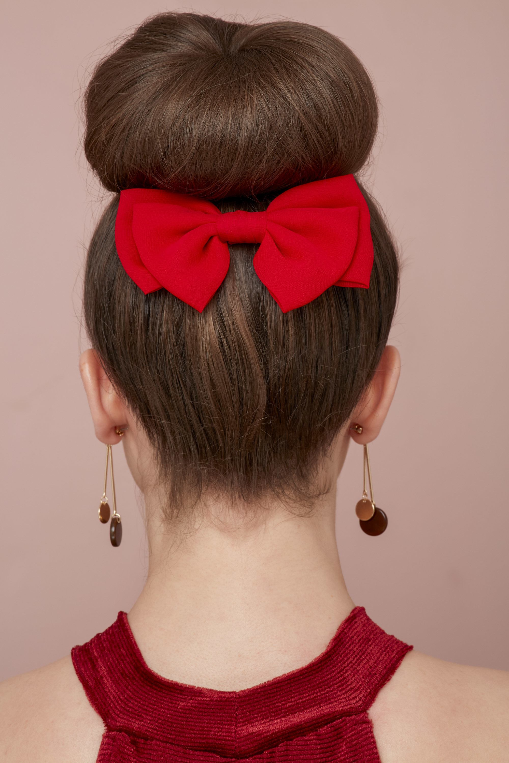 Valentines hair: Behind view of a brunette woman with her hair in a high ballerina bun with a red bow accessory, wearing a red dress