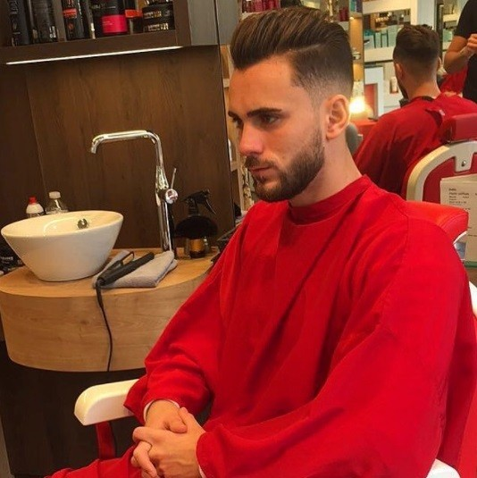 brunette man in a barbers chair wearing a red cape with a pompadour fade shaved haircut