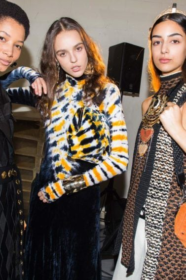 leave in conditioner for dry hair guide: close up shot of three models backstage, wearing proenza clothing NYFW