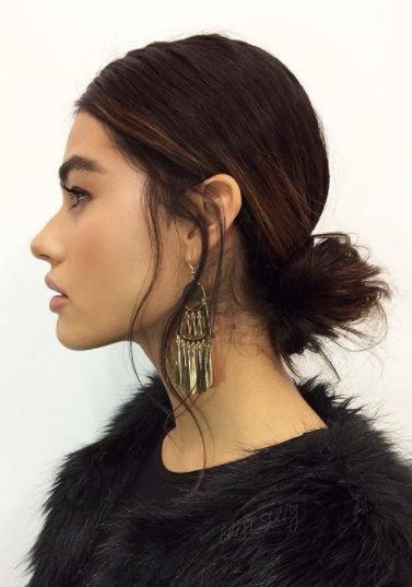 Hairstyles for long thin hair: Woman with dark brown hair in a low messy bun wearing all black and big earrings.