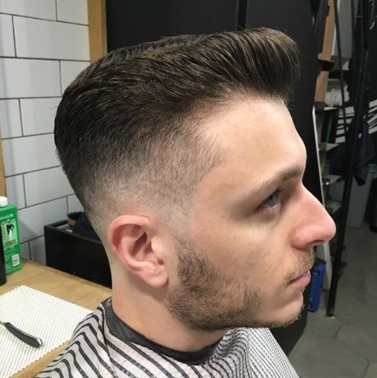 side profile picture of a man in a barbers chair with a stripy cape and a shaved pompadour fade haircut