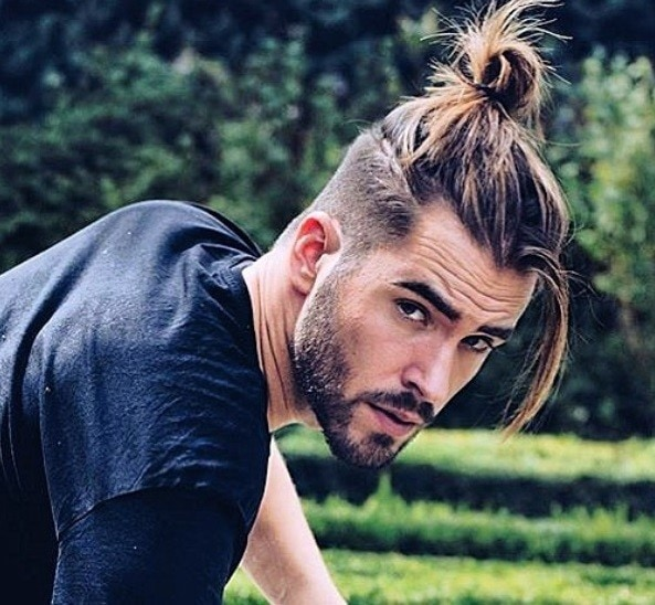 man bun haircut fade: close up shot of man with taper fade haircut, with some hair falling loose in front of his face wearing black shirt and posing outside