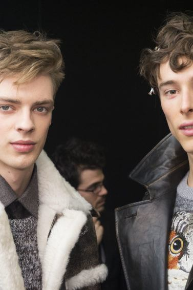 meet me at mcdonalds hair: close up shot of two male models backstage at the salvatore ferragamo with textured long tops and shaved sides