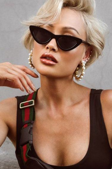 close up shot of woman with short pixie with side-swept bangs, wearing black top and posing with micro sunglasses