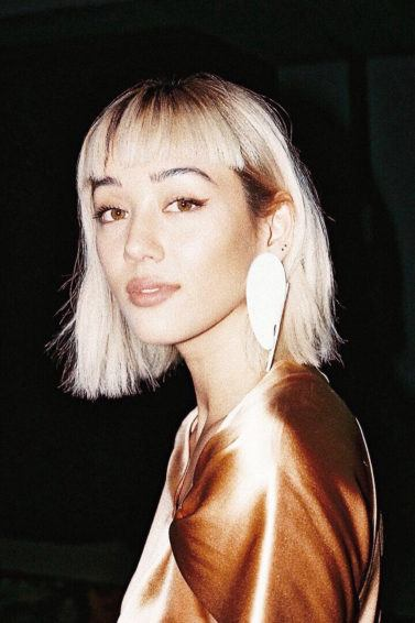 Types of bangs guide: Kim Jones with a bleach blonde long bob styled with a micro fringe, wearing a seashell earring with a satin orange top
