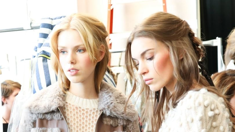 blonde and brunette models backstage at Zimmerman NYFW 2018 show with half-up, half-down hairstyle wearing nude and white coloured outfits