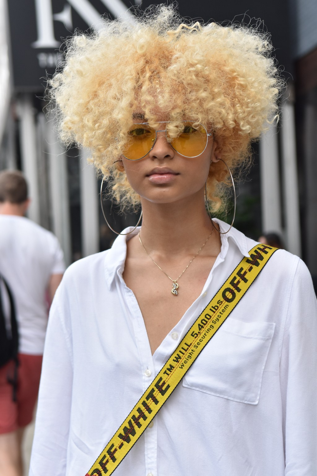 NYFW SS19 street style: Street style shot of a woman with a blonde afro wearing sunglasses and a white shirt