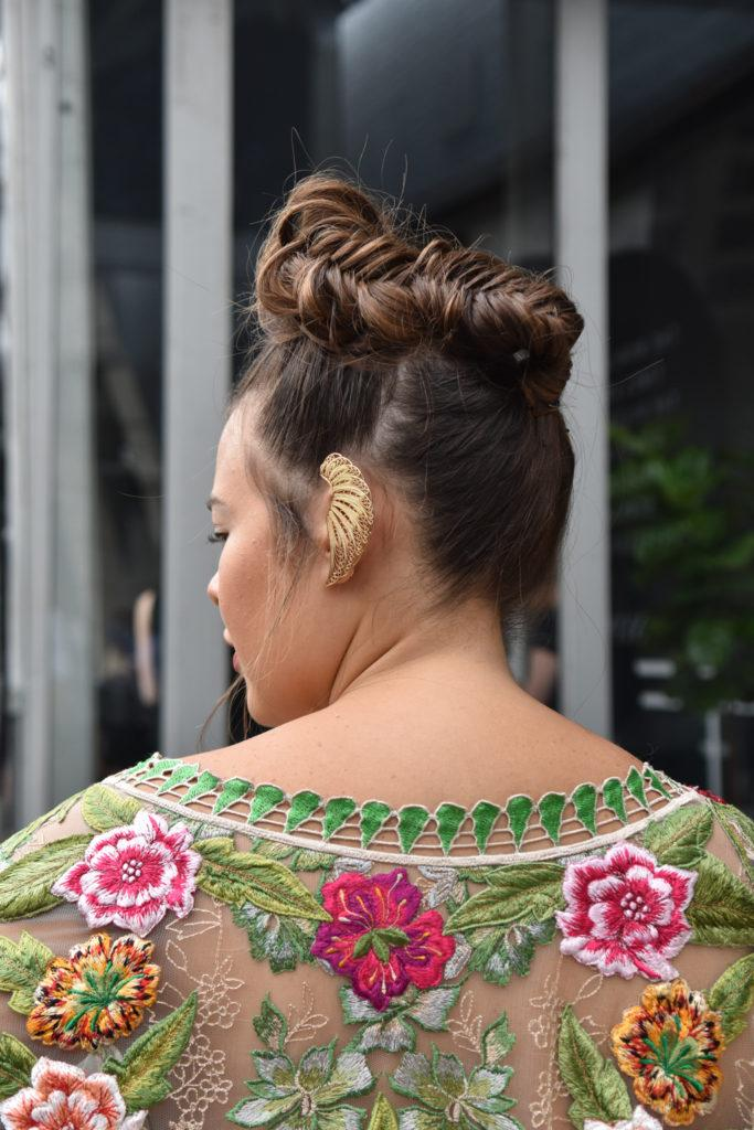 NYFW SS19 street style: Shot from behind of a brunette woman with her hair in a fishtail braided bun updo, with a gold ear cuff and floral top