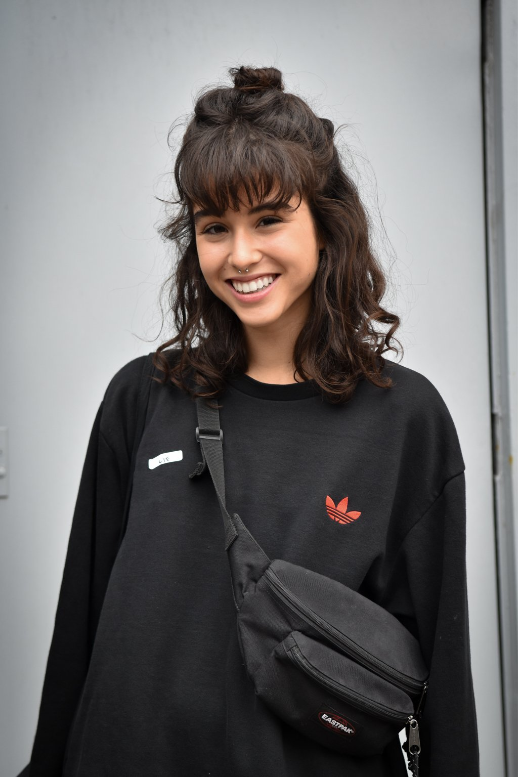 NYFW SS19 street style: Brunette with shoulder length wavy hair and a fringe styled in a half-up bun hairstyle