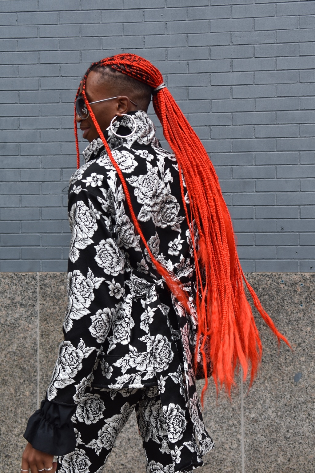 NYFW SS19 street style: Street style shot of a woman with long orange red box braids in a low ponytail hairstyle