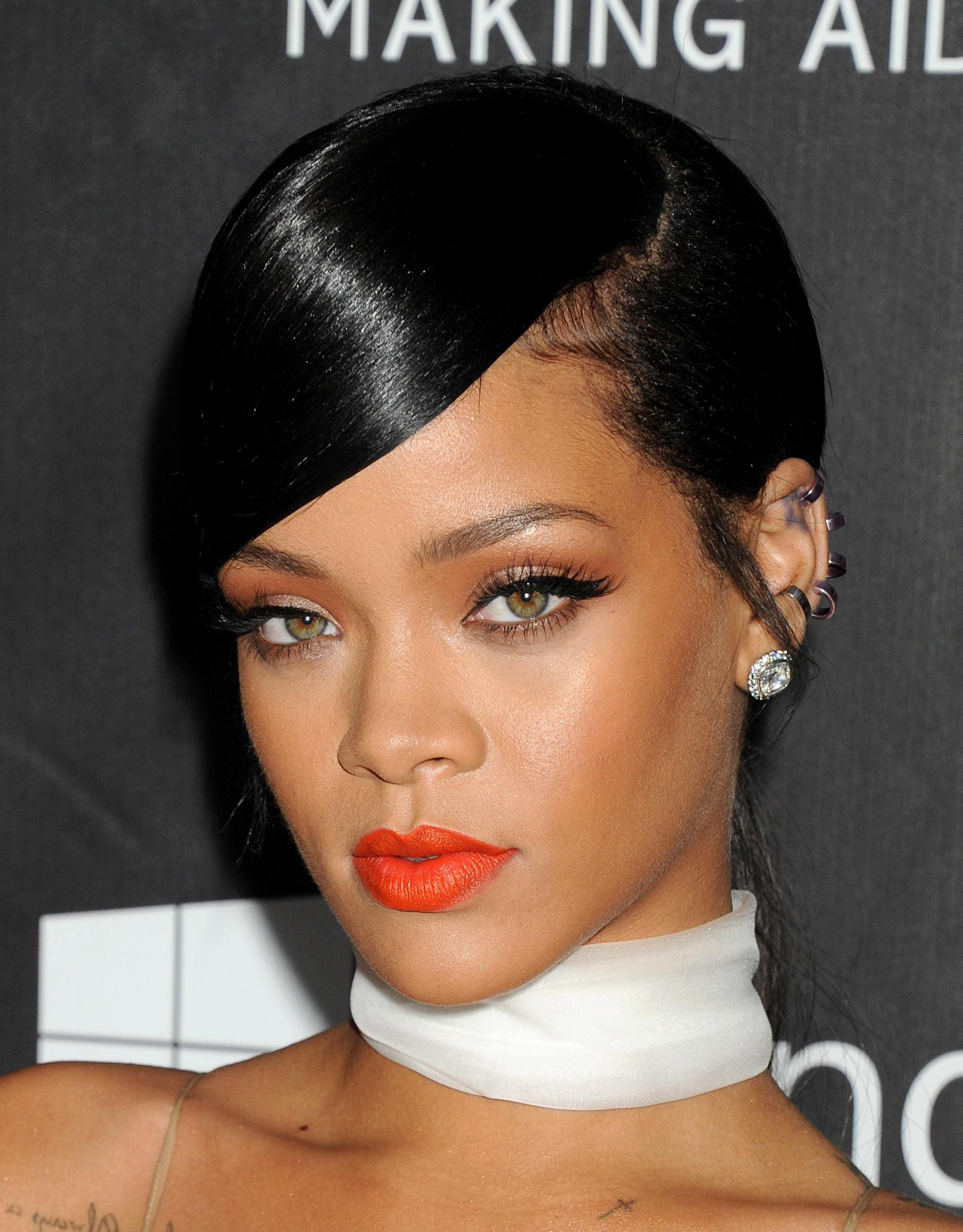 rihanna side parted updo with sweeping fringe on dark brown hair