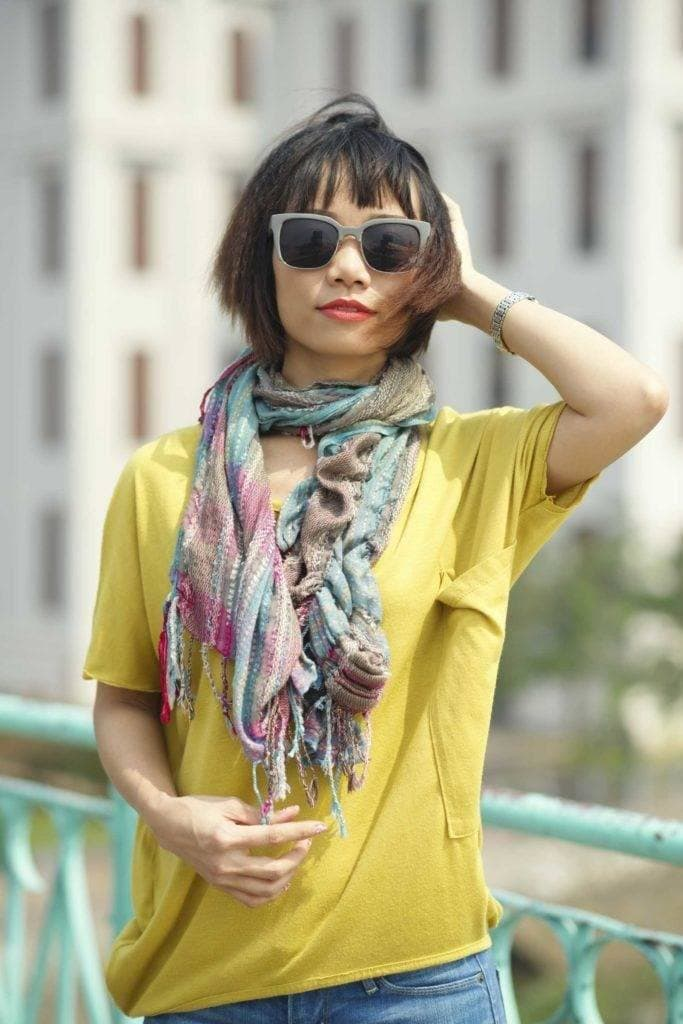 Asian hairstyles: Asian woman with bob and bangs with crimped finish wearing sunglasses.