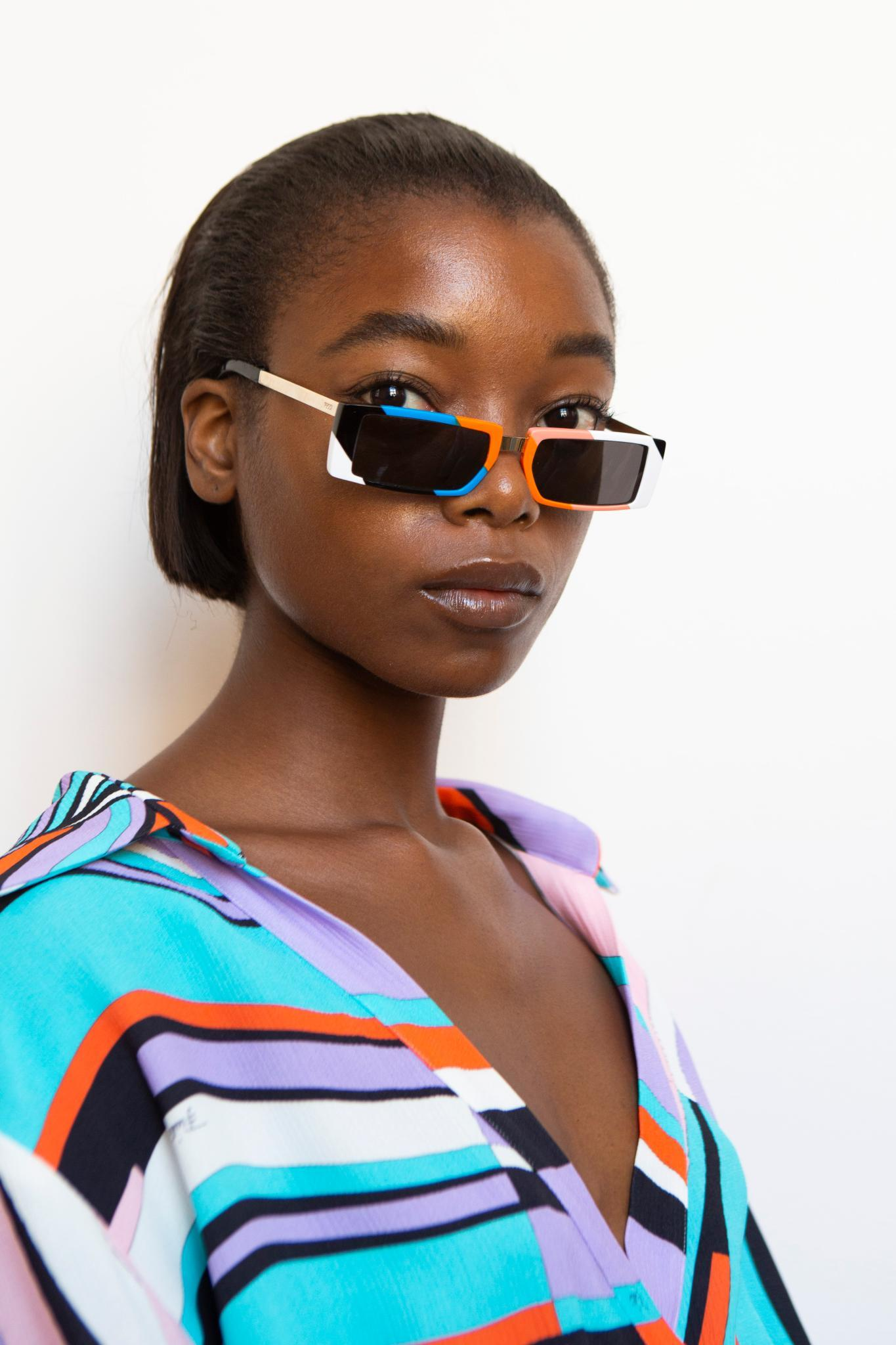 Short black hair ideas: black model with a straight combed back bob wearing glasses