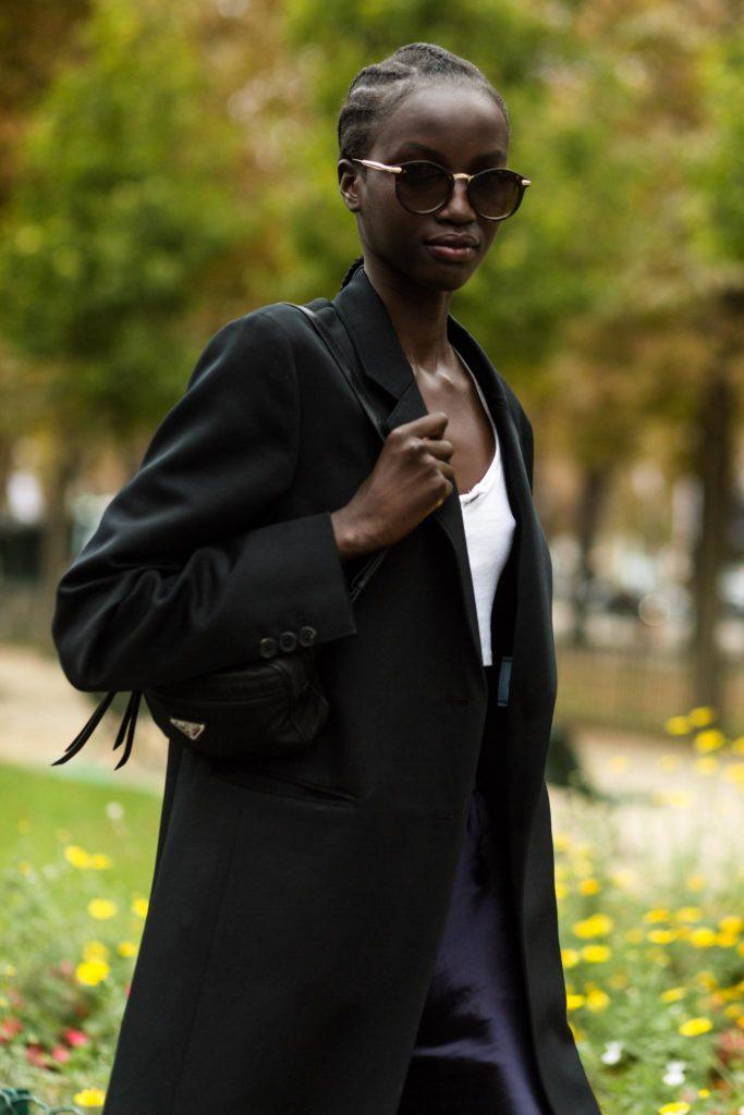 Short black hair ideas: A black model with cornrow hairstyle standing outside