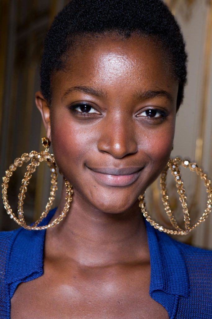 Short black hair: A model with a short afro wearing large statement gold earrings