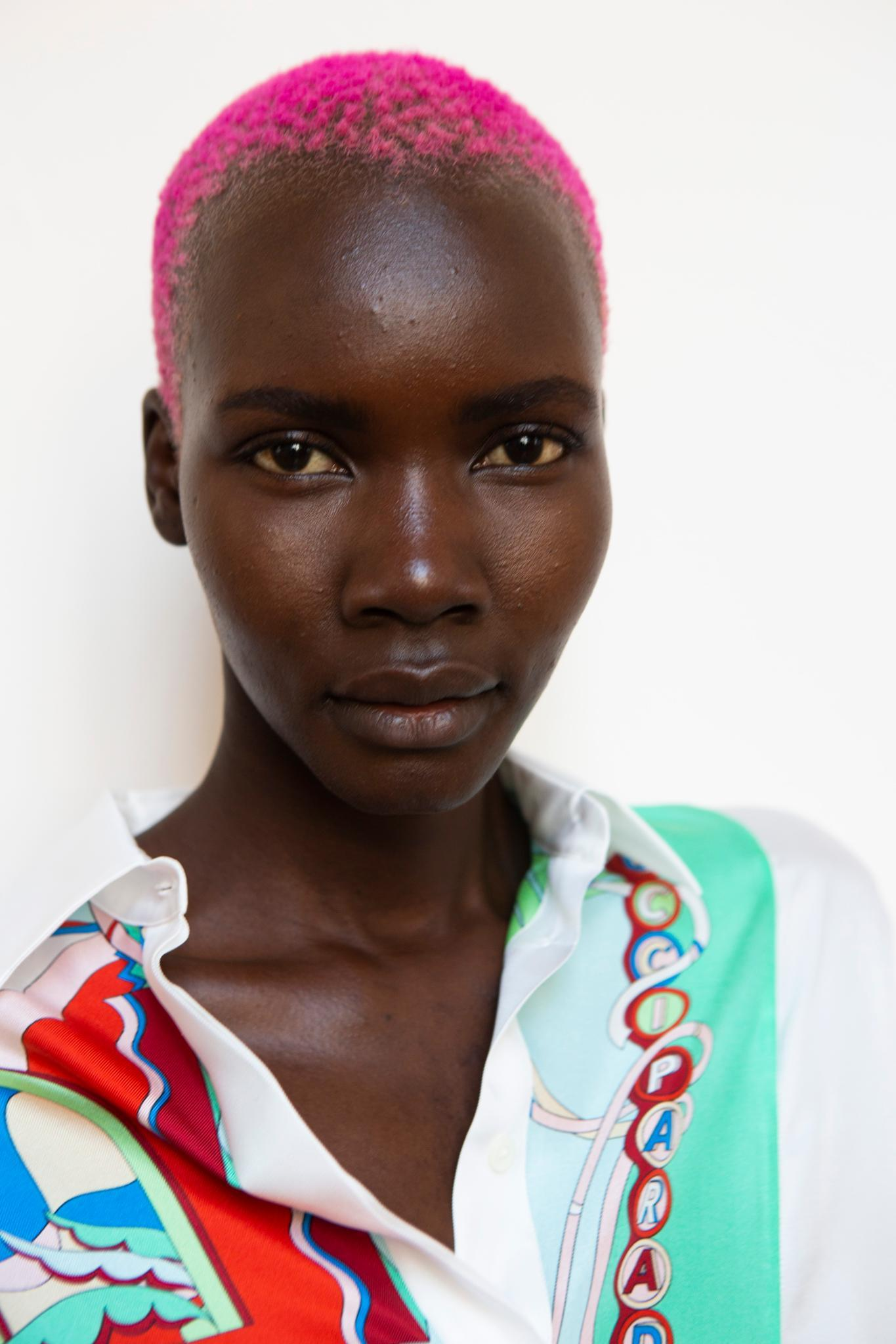 Short black hair: A black model with a shaved pink afro