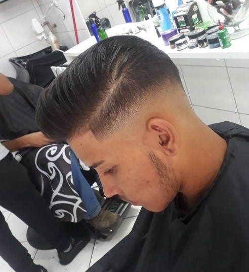 man in the barbers with brunette hair in a side parted pompadour fade cut