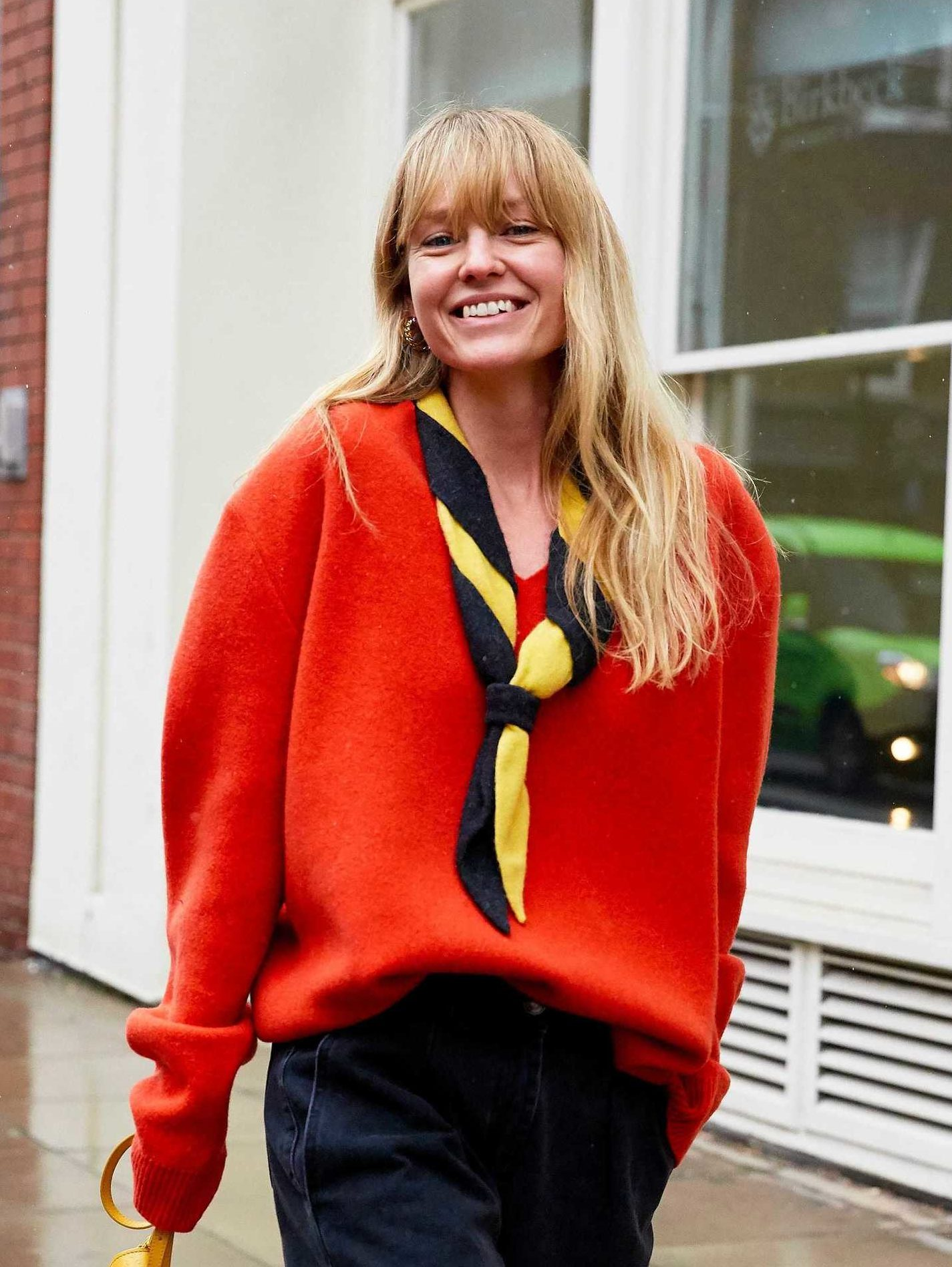 Spring haircuts: Blonde street styler with mid length wavy hair and a full fringe, wearing an orange red jumper and a striped neck scarf, standing outside in the street