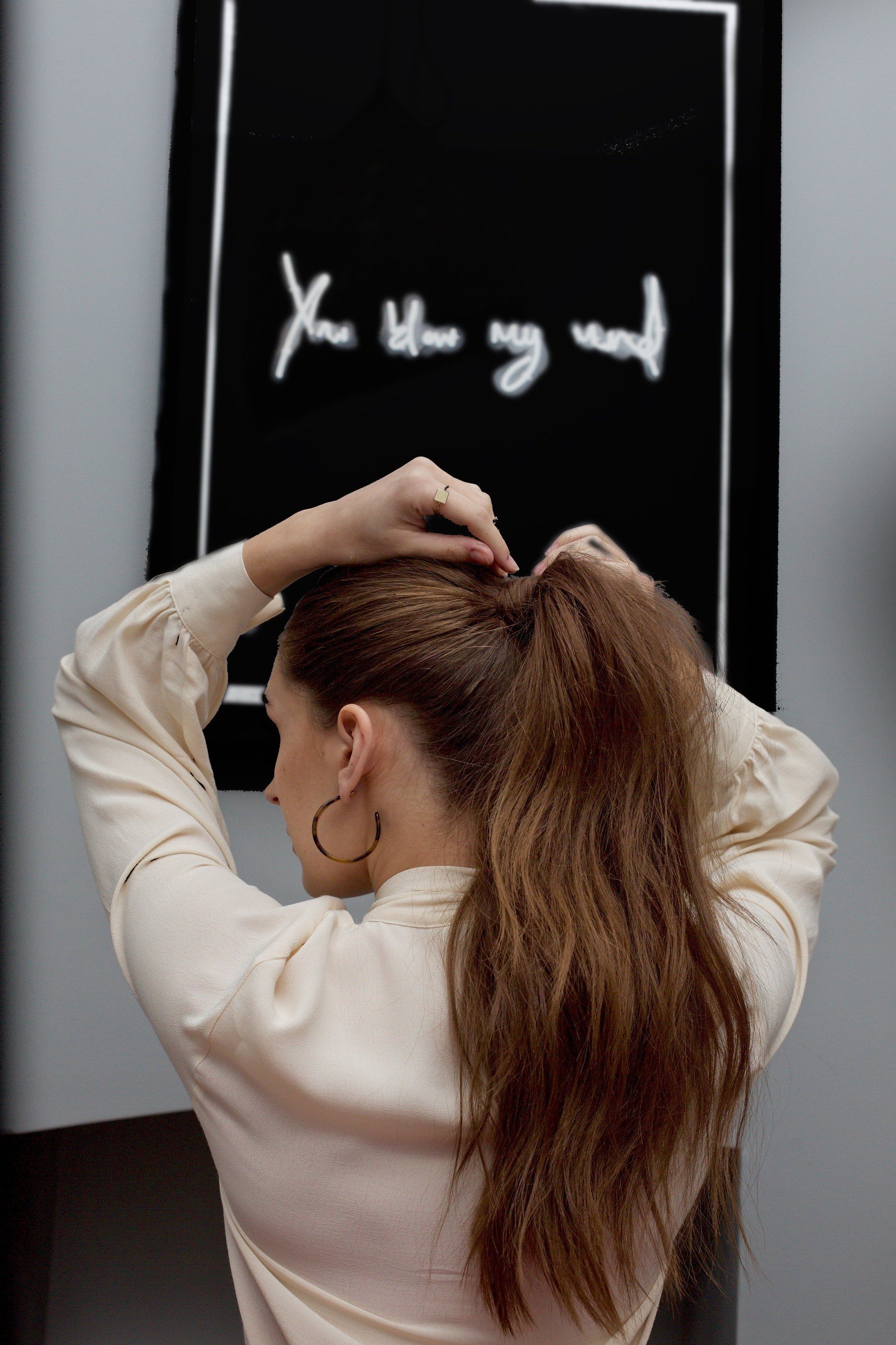 Spring haircuts: Back view of a brunette woman with a long voluminous wavy ponytail, putting a bobby pin in her hair and wearing a cream blouse