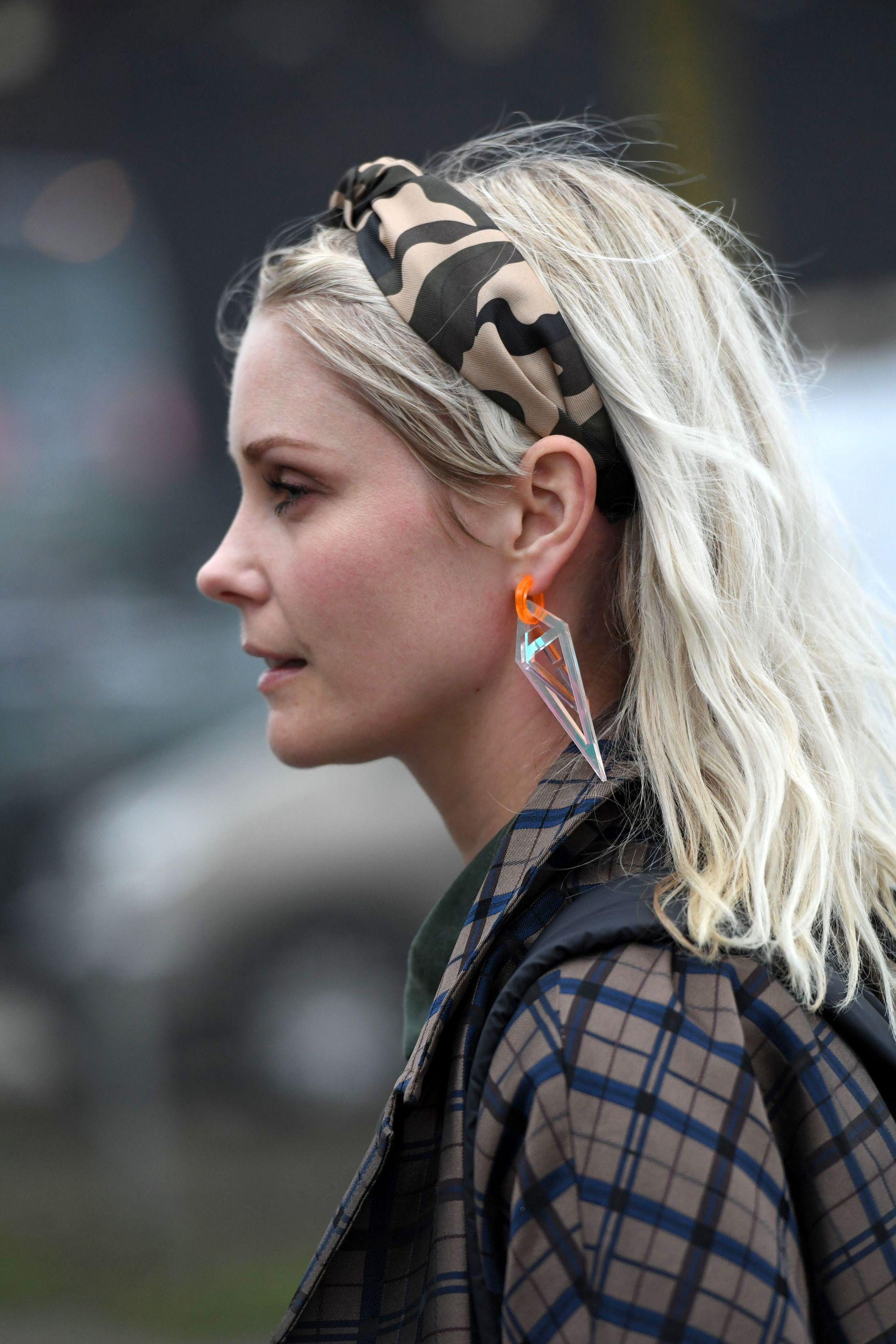 Spring haircuts: Side profile street style shot of a woman with mid length ash blonde hair with a camo leopard print headband