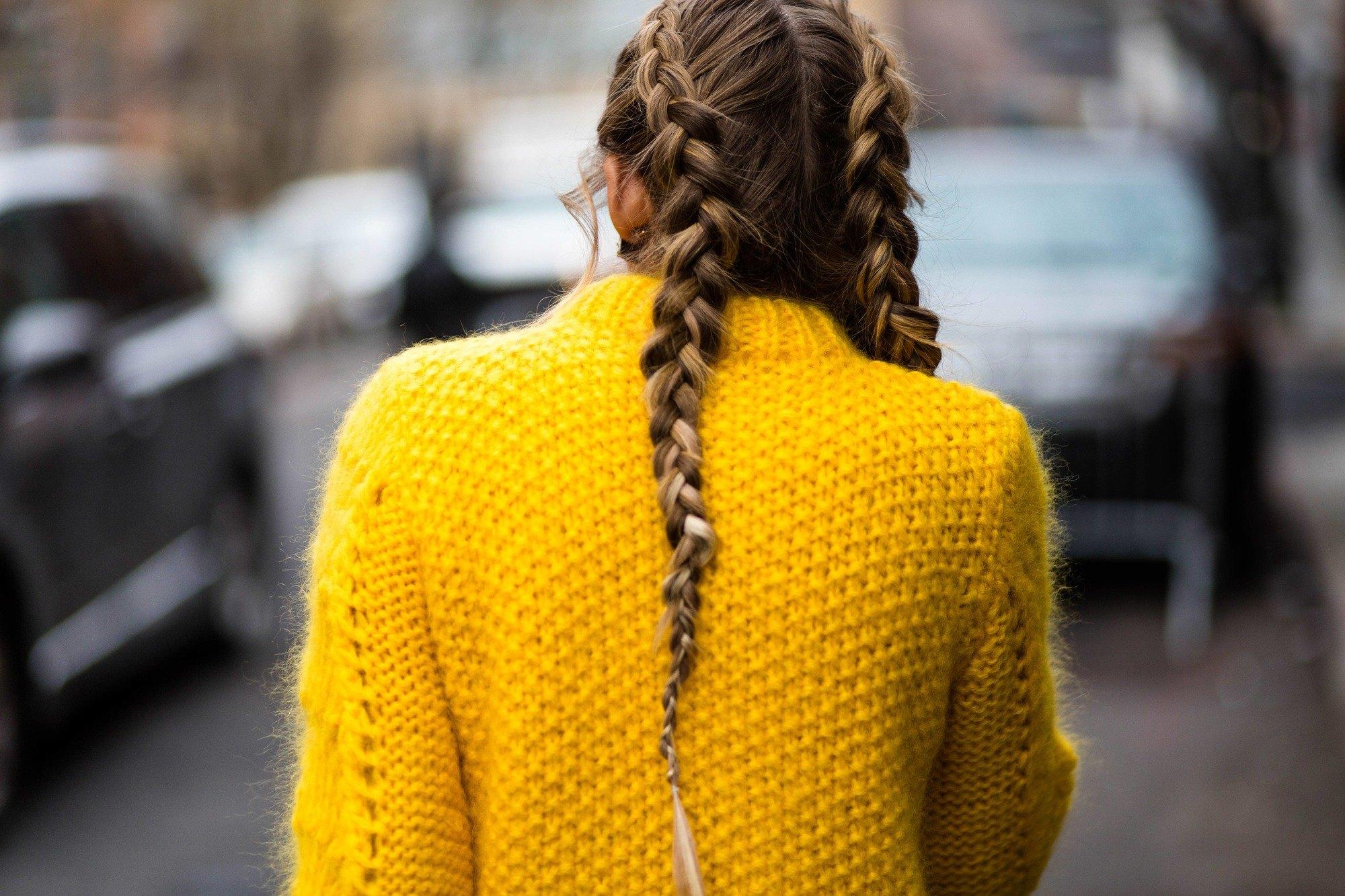 Brunette woman walking outside fashion week with boxer braids